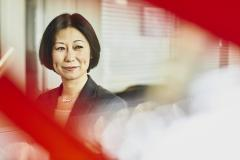 Woman in suit smiling. Japan. Primary color: red.