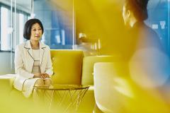 Women in an office talking. Japan. Primary color: yellow.